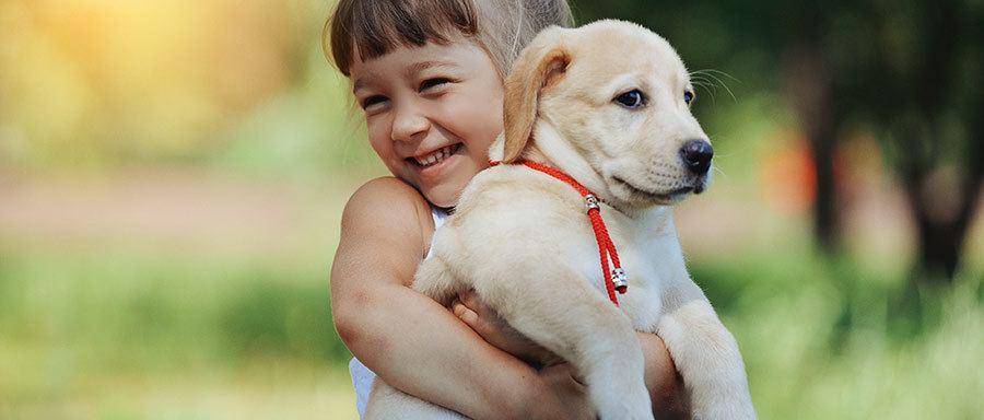child squeezing puppy
