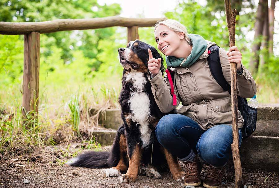 woman bonding with dog while walking and hiking
