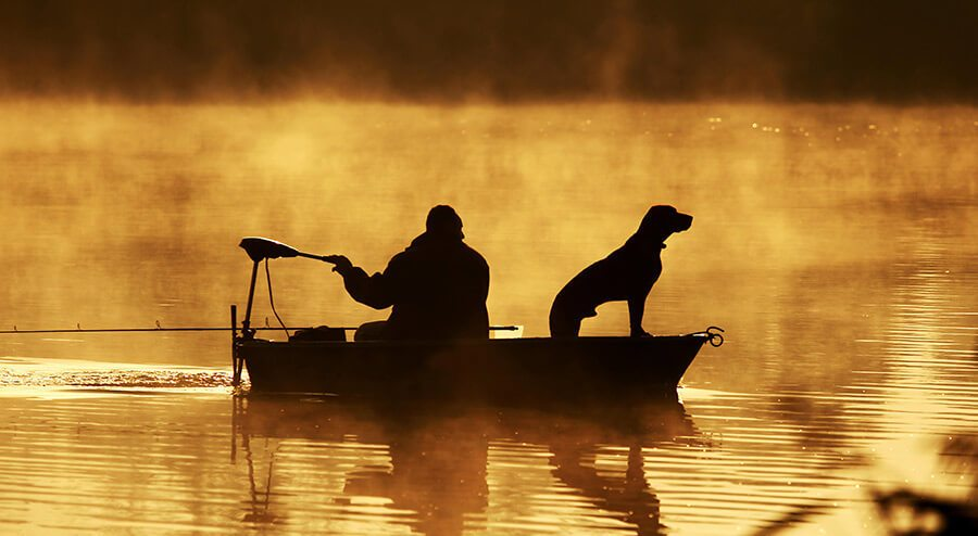man with dog fishing in boat