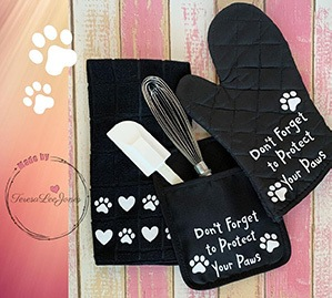 dog matching kitchen black towel and pot holders, paw prints and says Don't forget to protect your paws.